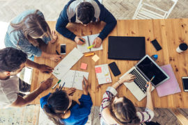 overhead view on young business people around wooden desk